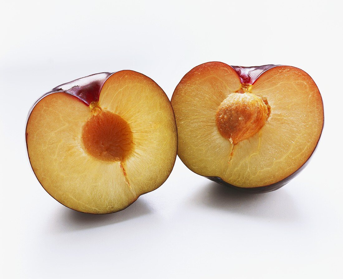 Two plum halves, one with stone