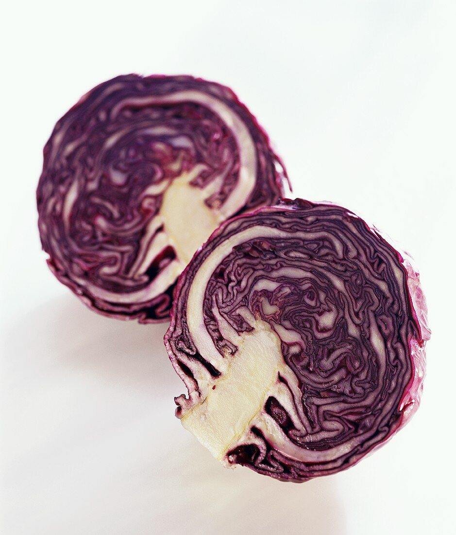 Two red cabbage halves on white background