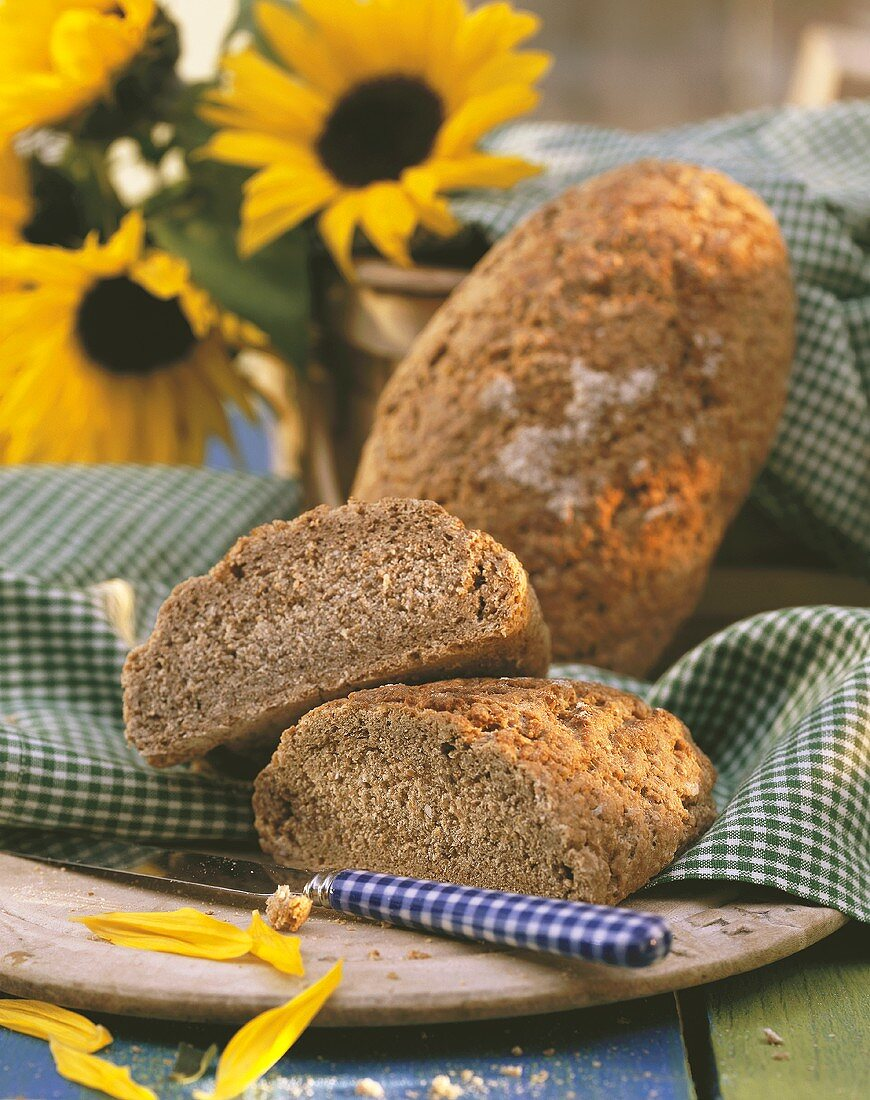Graham bread, half & whole loaf, on wooden plate with cloth