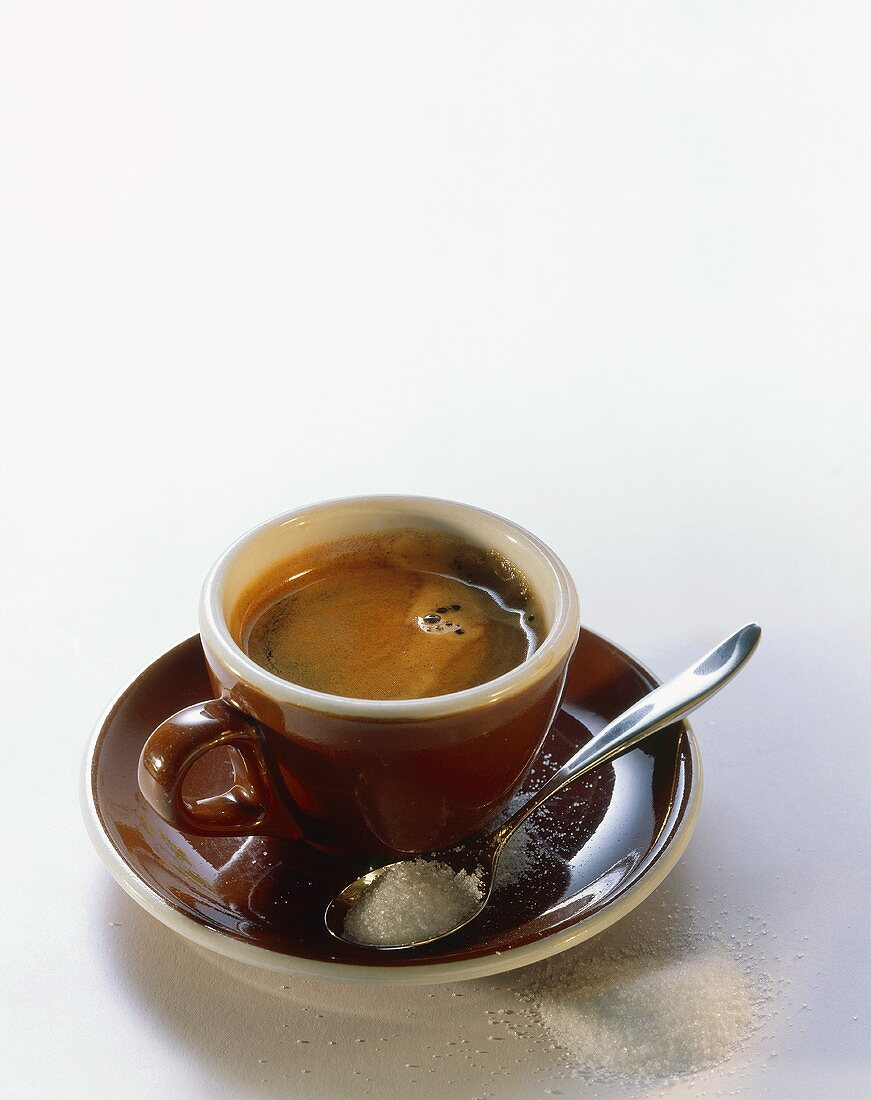 Espresso in brown cup; spoon with sugar in saucer