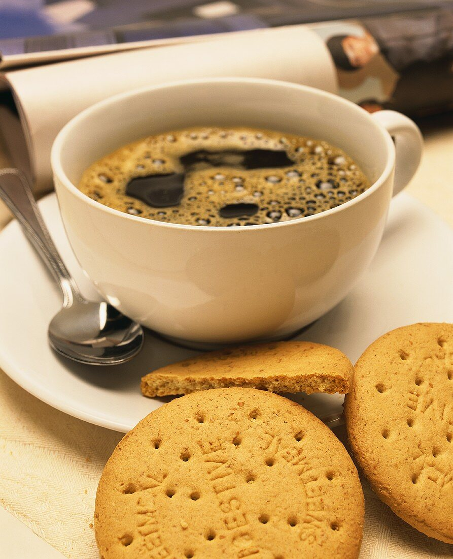 A cup of black coffee & a few biscuits; decoration: newspaper