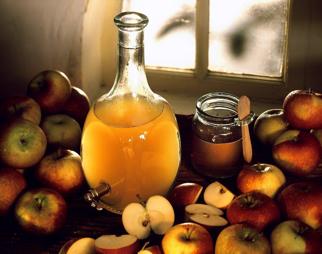 Apple vinegar in bottle, a jar of honey & fresh apples