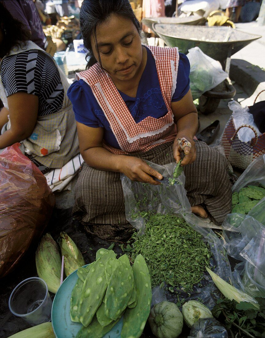 Woman with Cactus Fig Leaves at a Market in Mexico