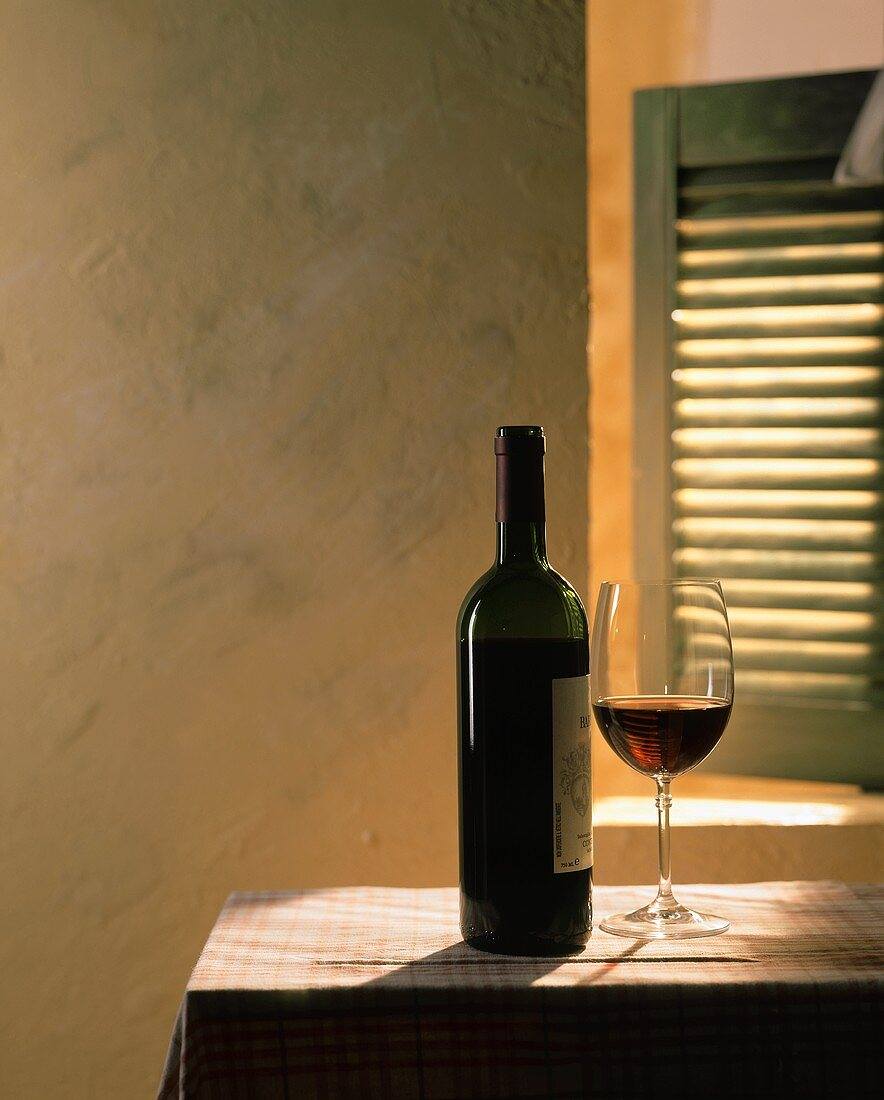 Red wine in bottle and glass on table in front of a window