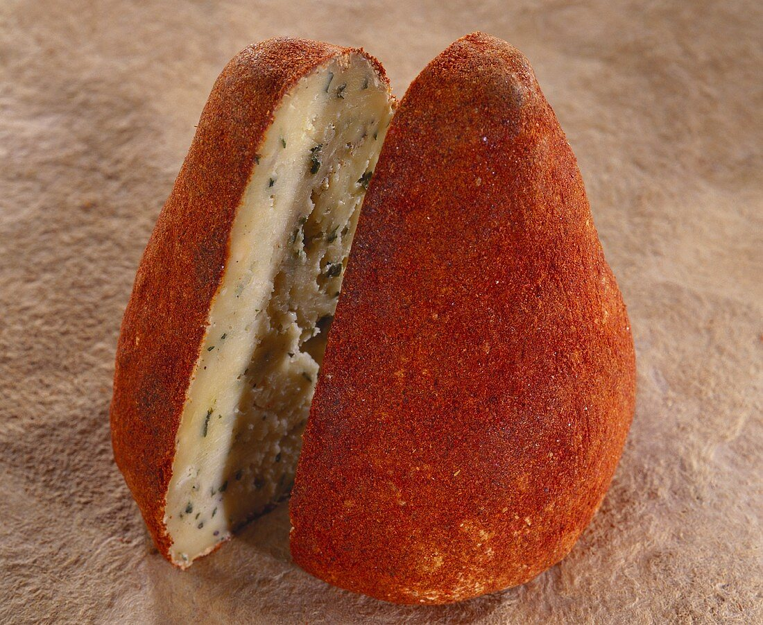 Boulette d'Avesnes, a cone-shaped cheese, on brown background