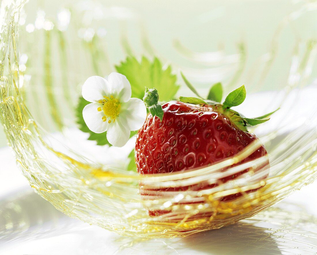 A strawberry with strawberry flower in a basket of caramel strands