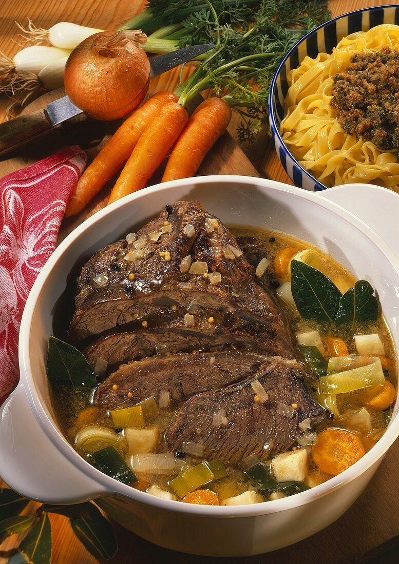Braised pickled beef with vegetables in pot on chopping board