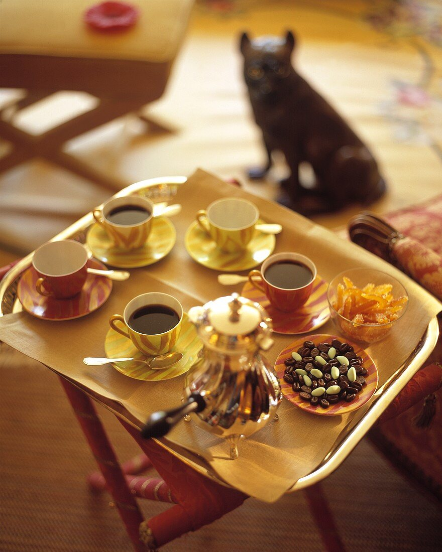 Coffee on a tray with pralines and candied oranges
