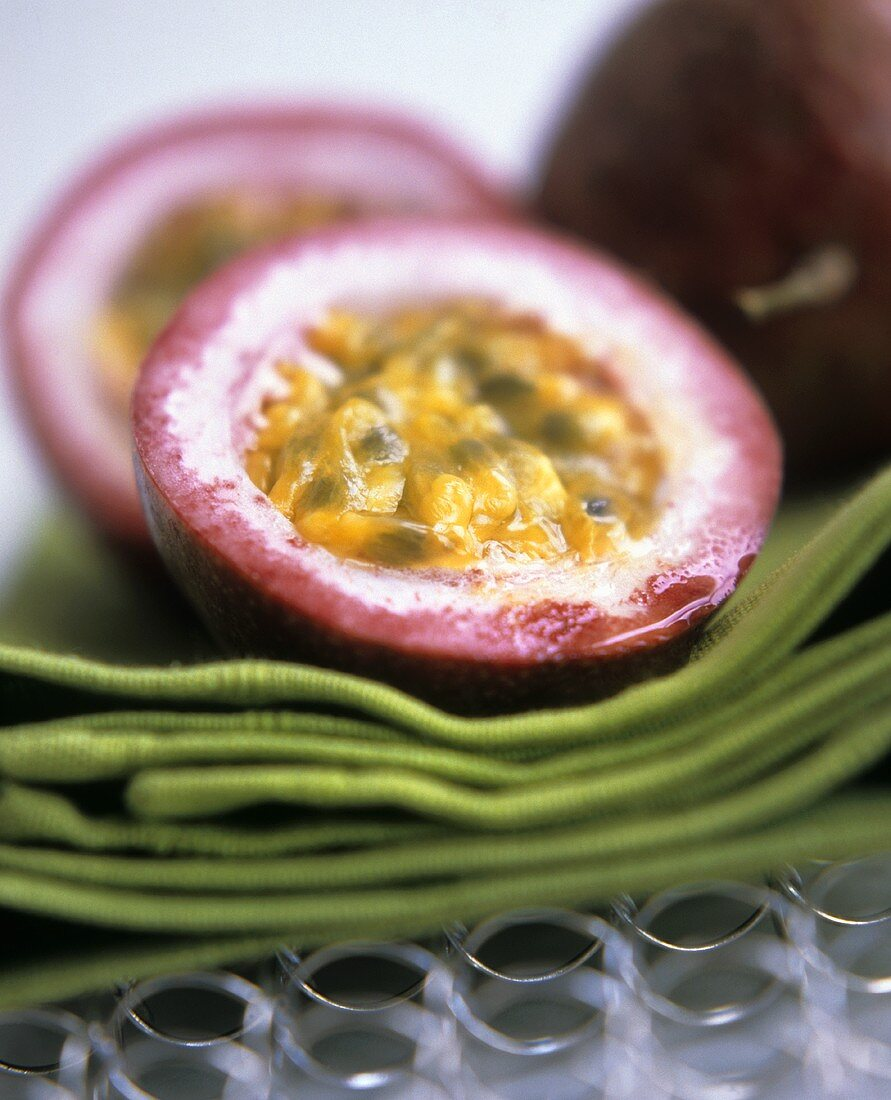Halved passion fruits on green napkins