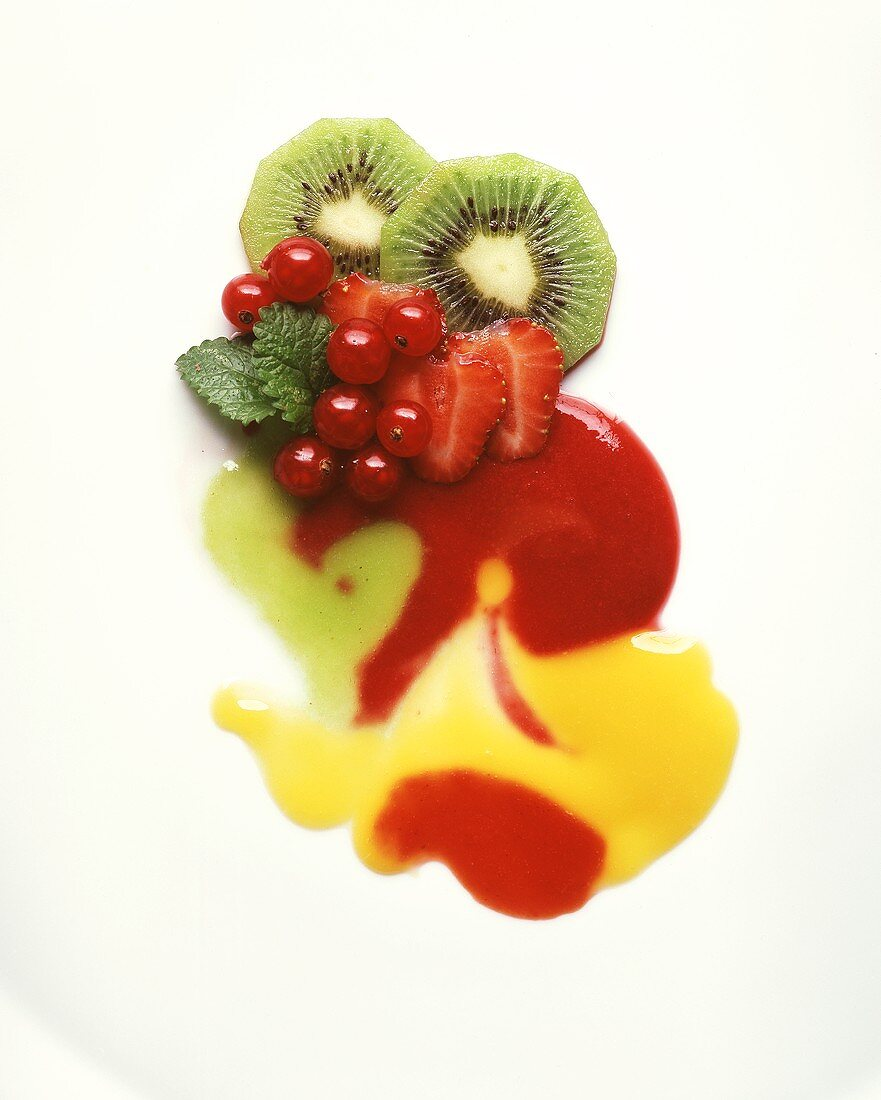 Kiwi fruits, strawberries and redcurrants with fruit sauces