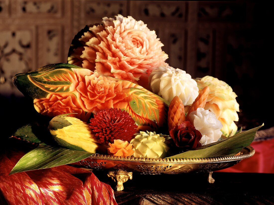 Flowers carved from fruit and vegetables in a bowl