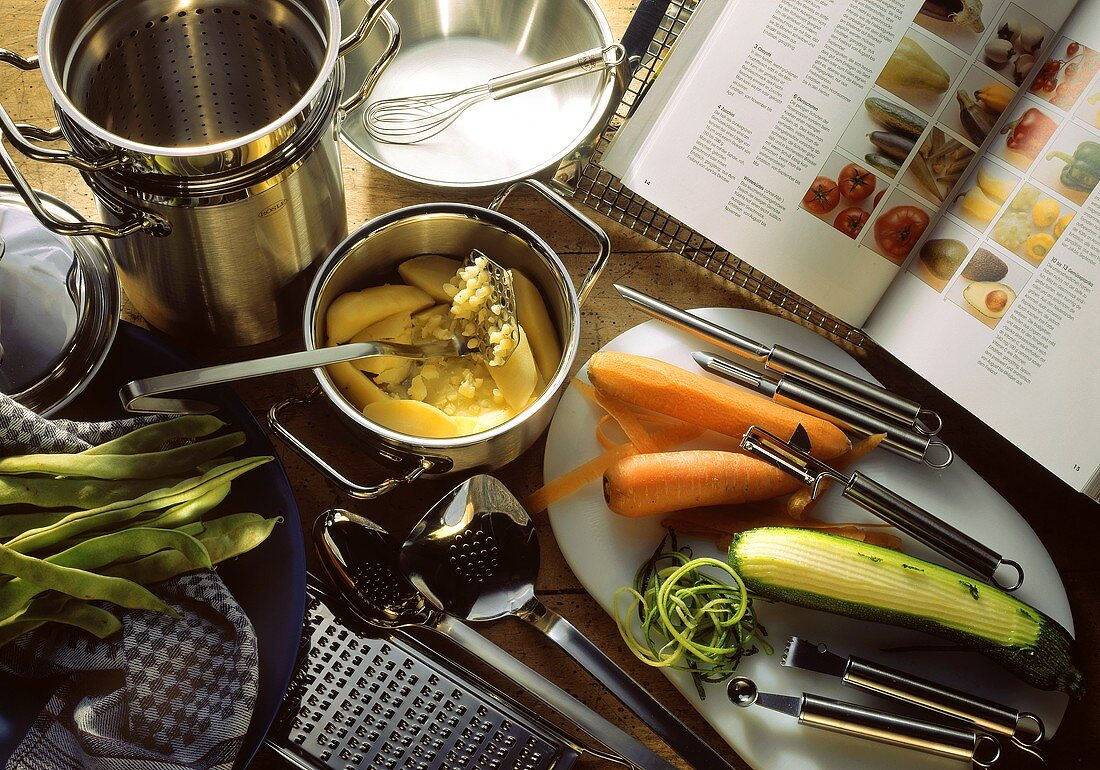 Kitchen utensils for cooking vegetables; open cookery book