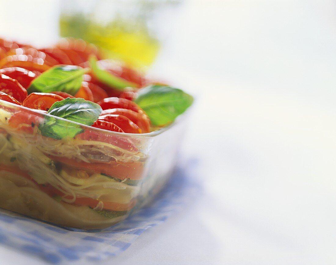 Potato & vegetable gratin with olive oil, basil in glass dish