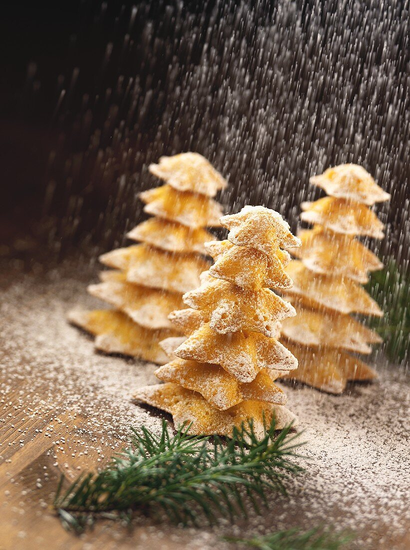 Fir tree biscuits being sprinkled with icing sugar