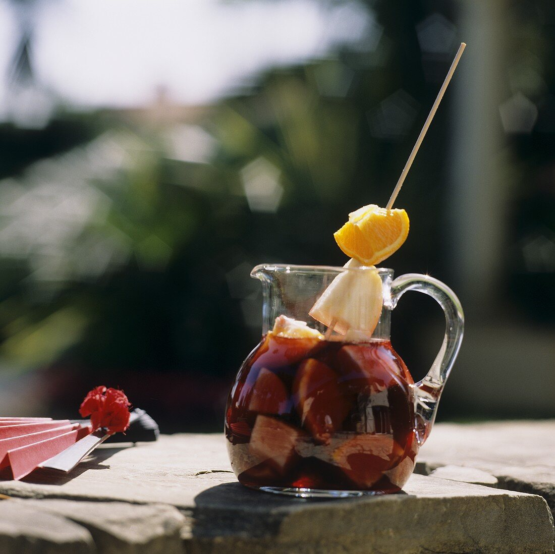 Sangria in glass jug on stone wall, a fan beside it