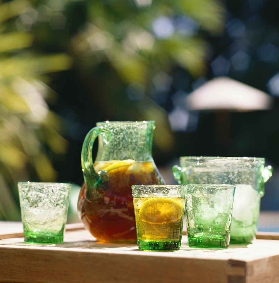 Iced tea with lemon in glass jug on table; glasses; ice bucket