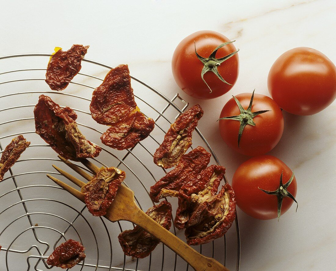 Fresh tomatoes beside dried tomatoes on trellis