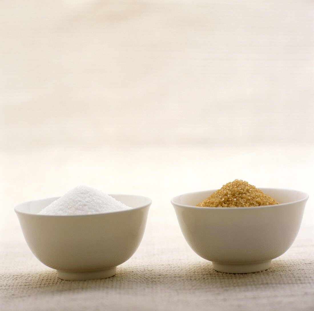 Brown and white sugar in white bowls