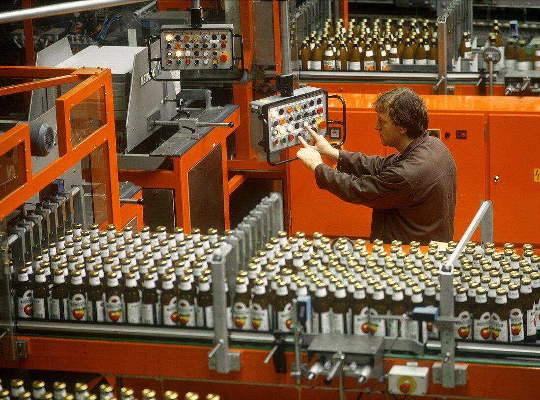 Arbeiter an der Abfüllmaschine in Getränkefabrik