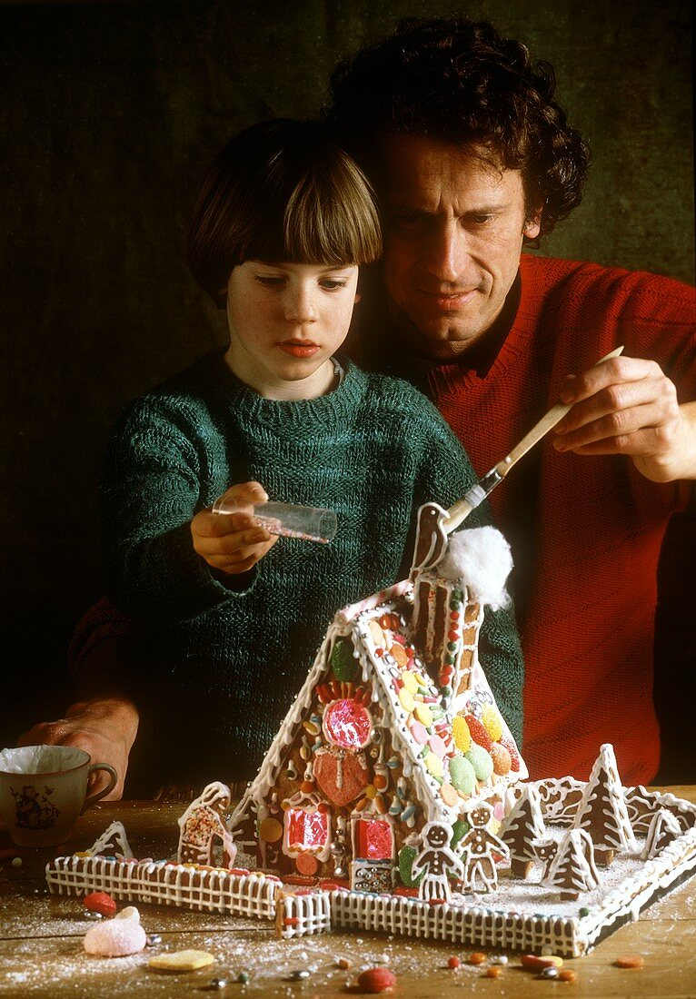 Father and child decorating a gingerbread house