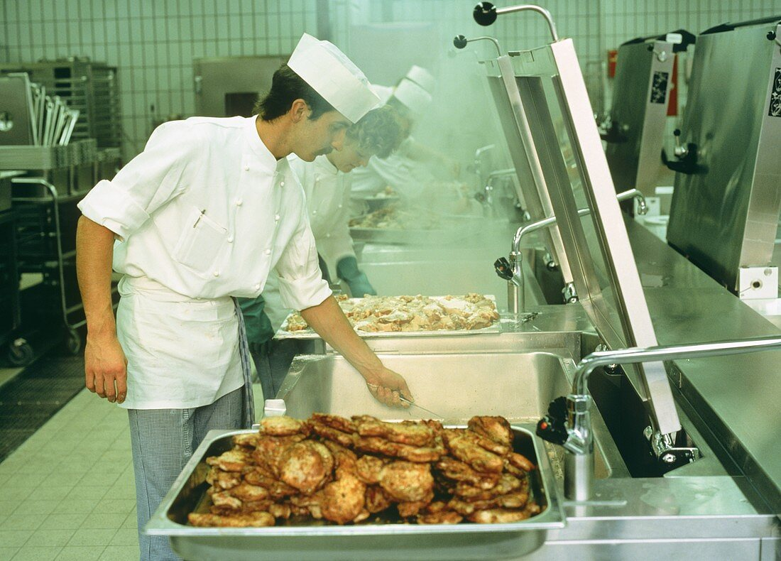 Chef frying meat in the kitchen of an industrial company