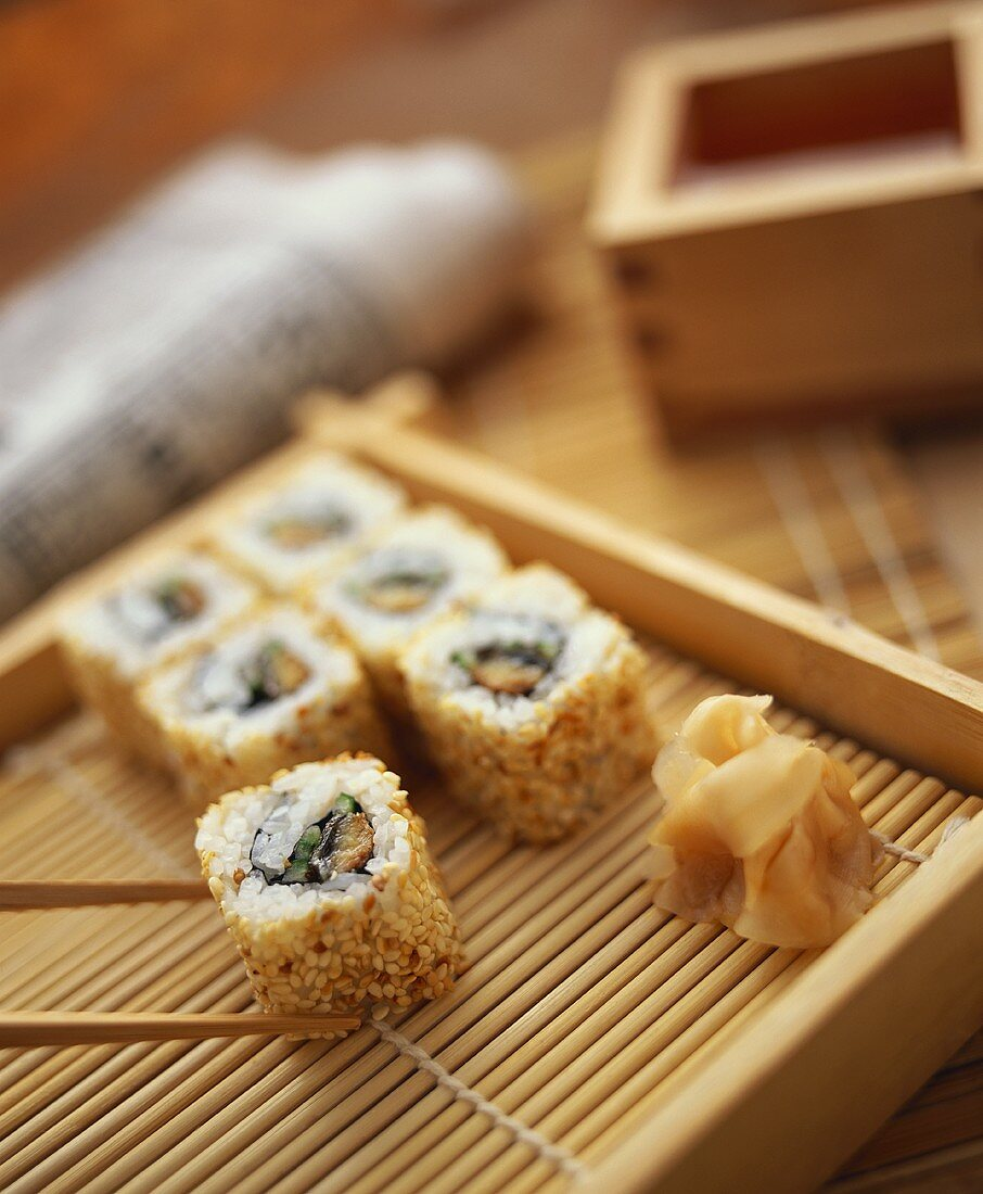 Ura maki (inside out roll) on bamboo tray with ginger