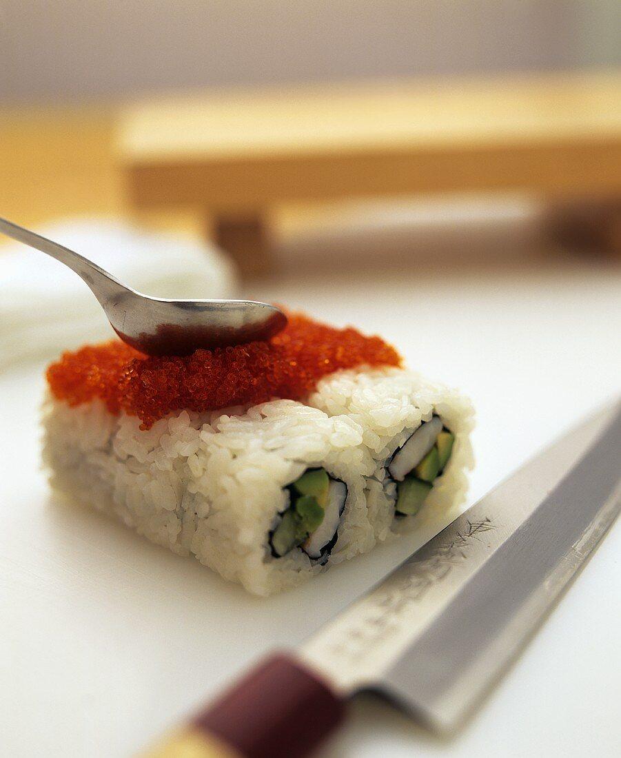 Preparing ura maki: spreading caviare with a spoon