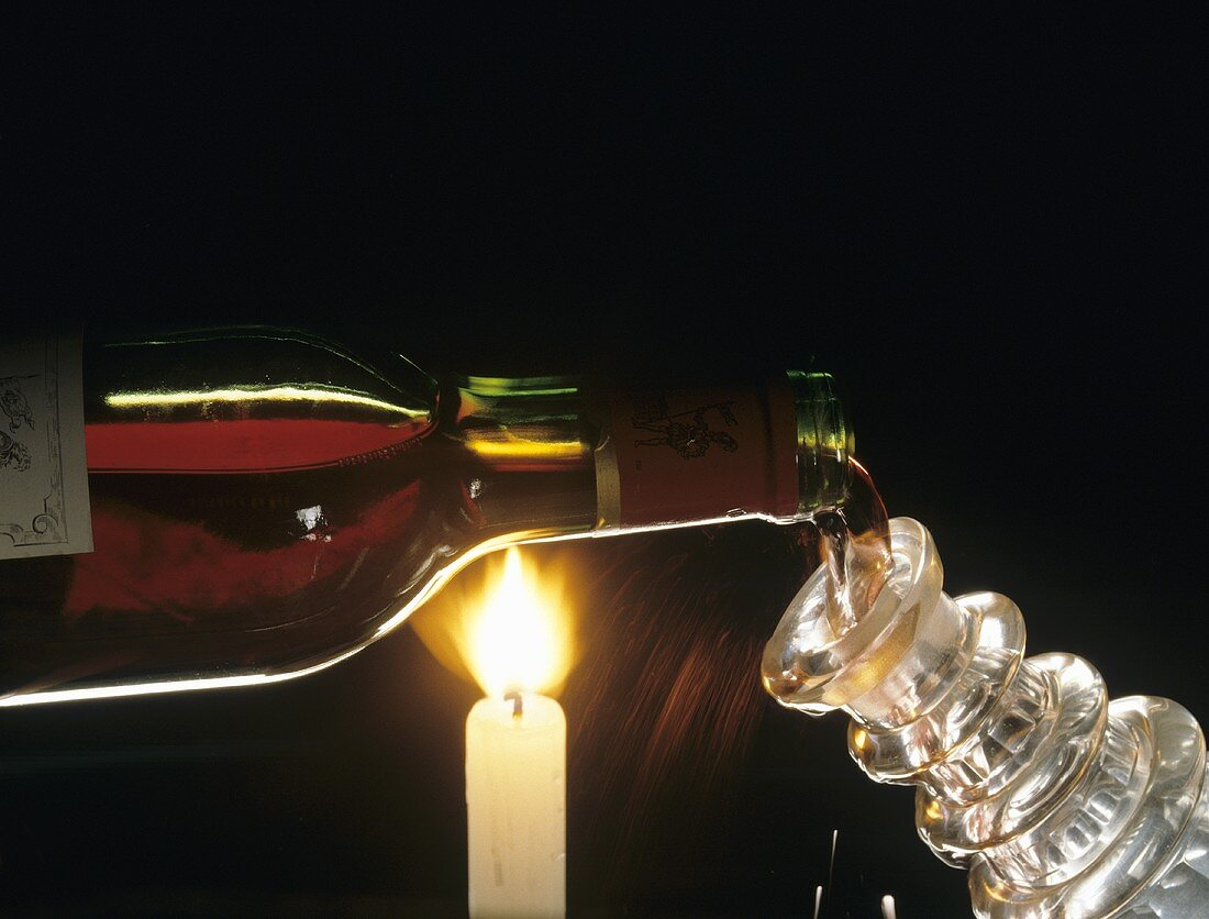 Filling carafe with red wine over candle flame