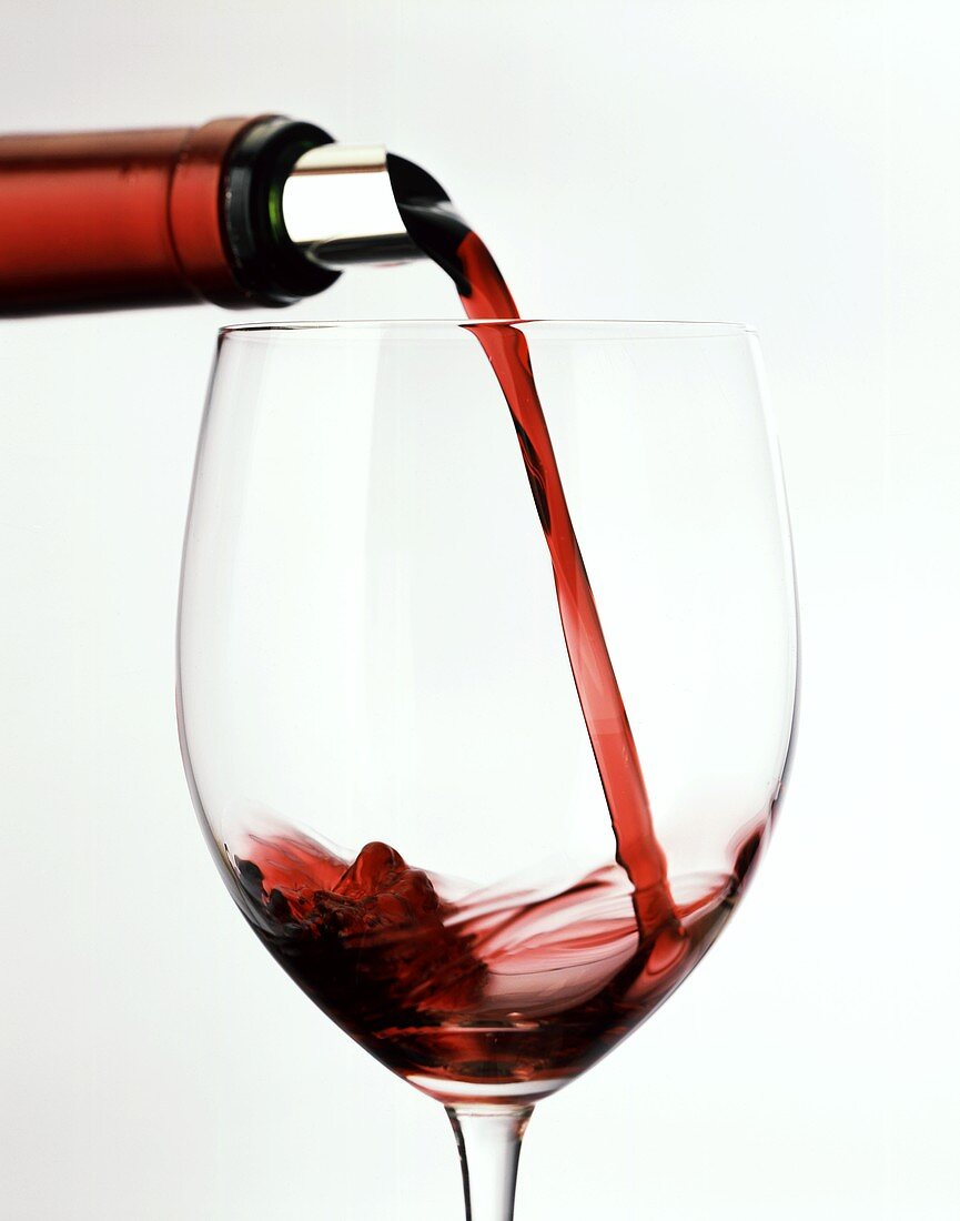 Pouring red wine from bottle with silver foil into glass