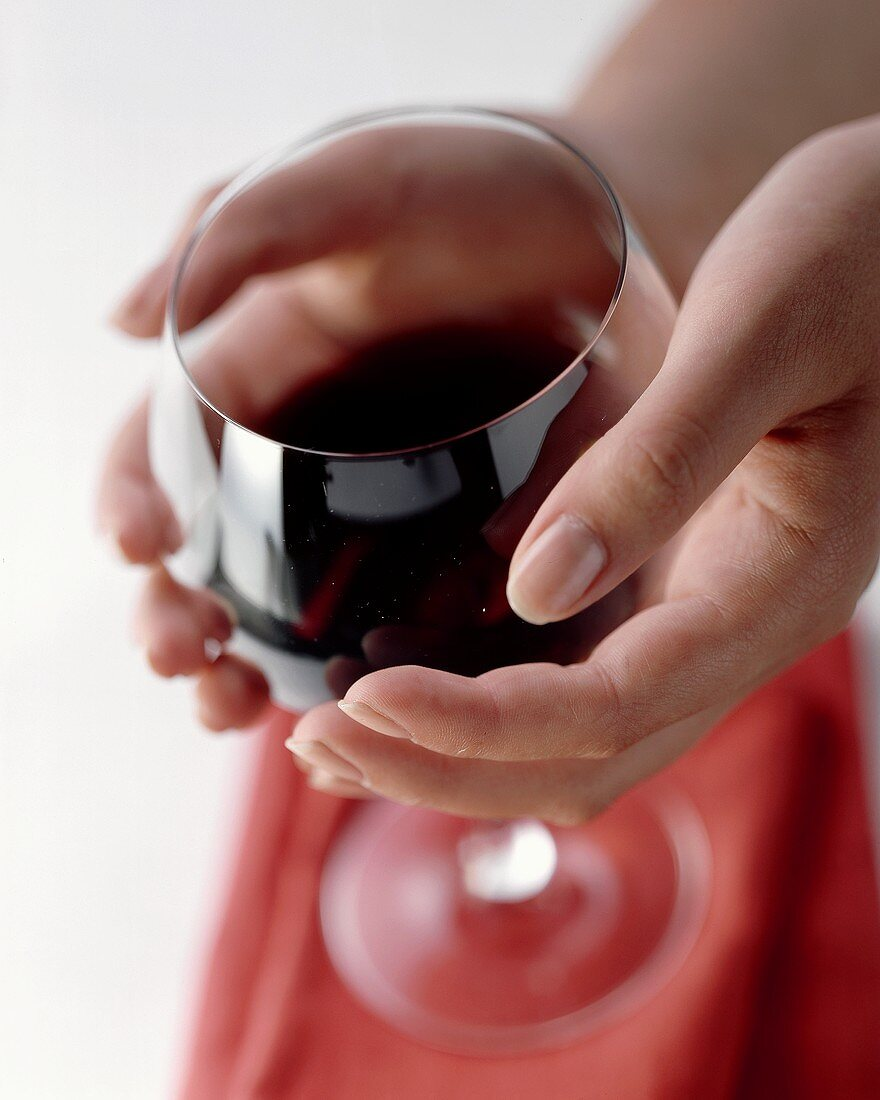 Warming red wine in the glass with the hands