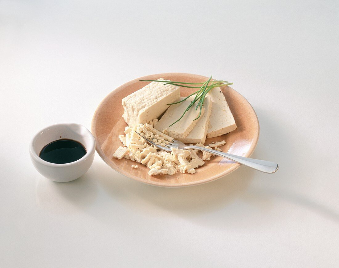 Tofu on plate and a bowl of soya sauce