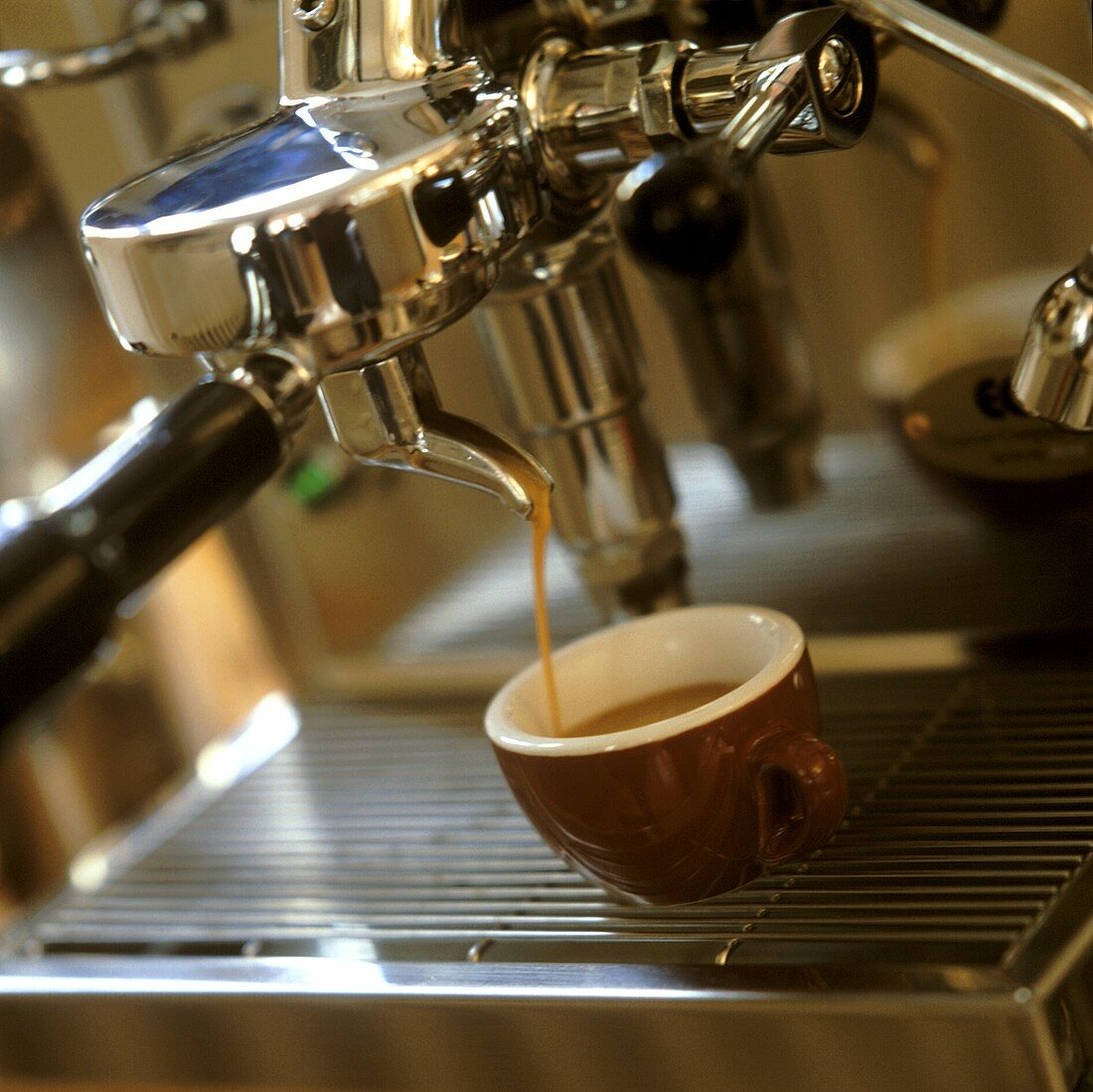 Espresso running out of espresso machine into brown cup
