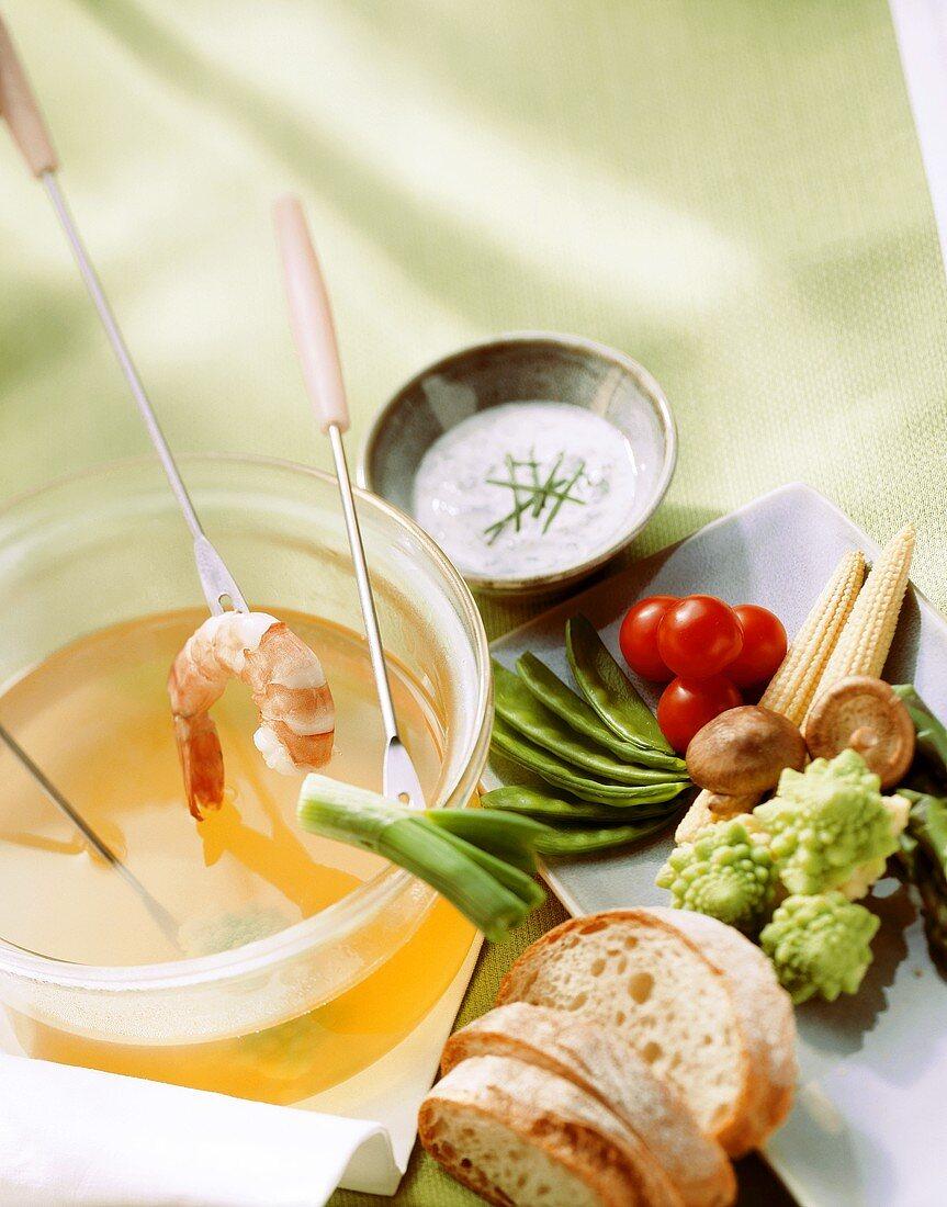 Fondue with vegetables, shrimp, bread slices & herb dip