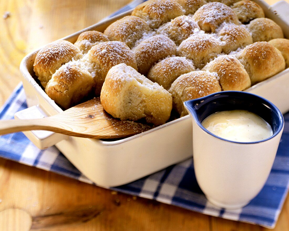 Freshly baked yeast rolls in baking tin; vanilla sauce