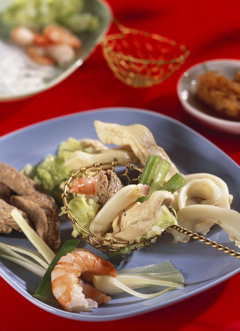 Asian fondue with meat, poultry, shrimps, vegetables