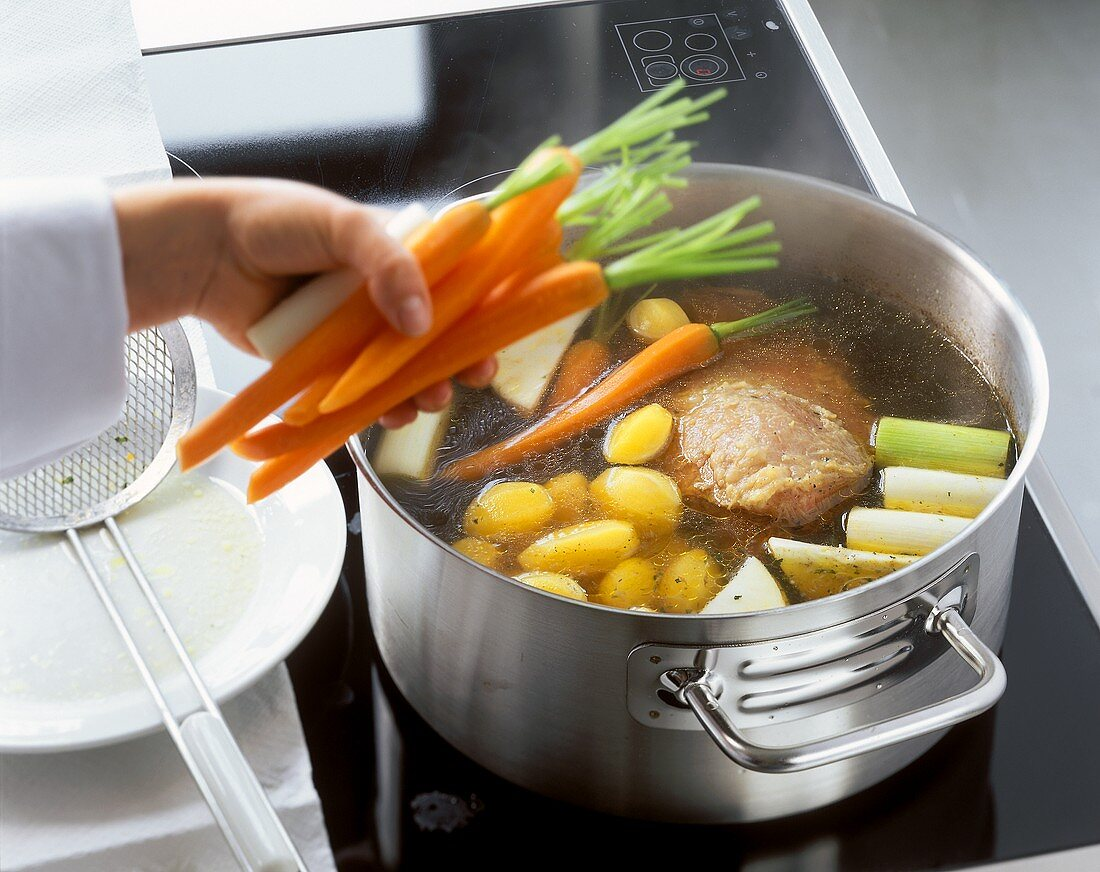 Adding vegetables to the beef fillet in the stock