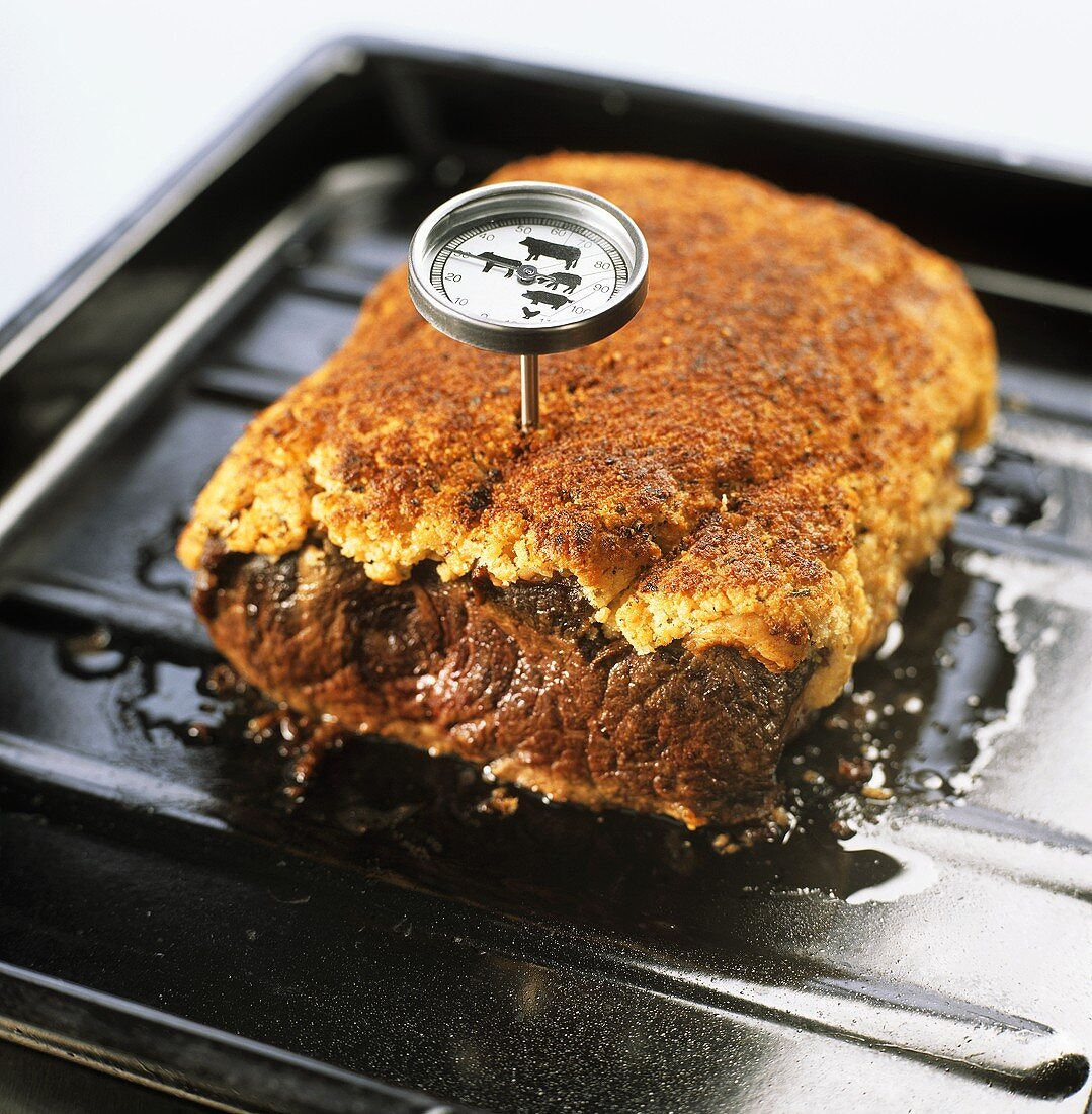 Checking internal temperature of roast with meat thermometer