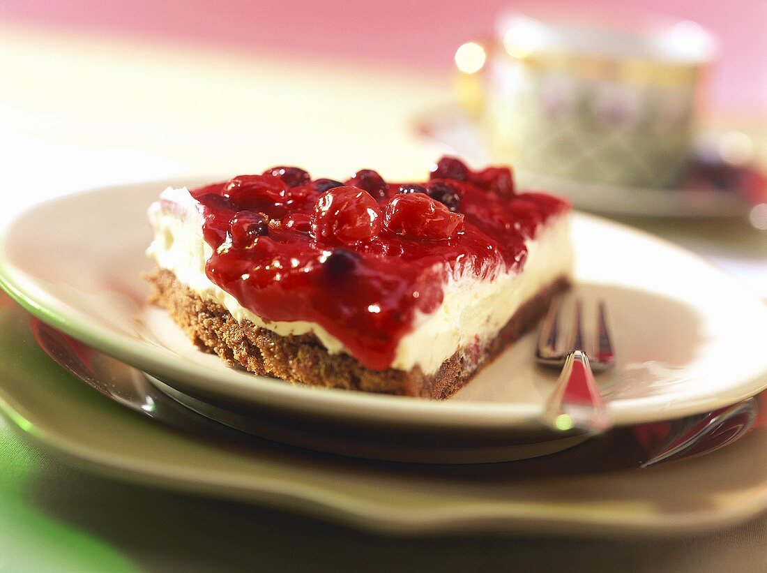 Piece of cheesecake with red berry compote
