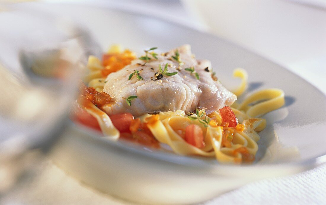 Red perch on tagliatelle with tomatoes