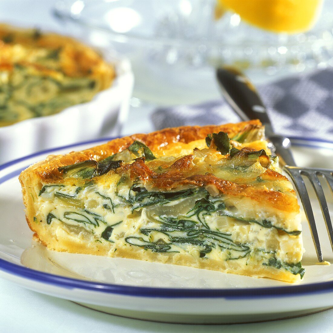Piece of chard quiche on plate in front of baking dish