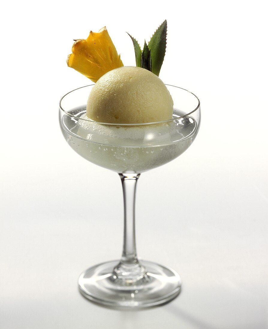 Pineapple ice cream in champagne glass with fresh pineapple