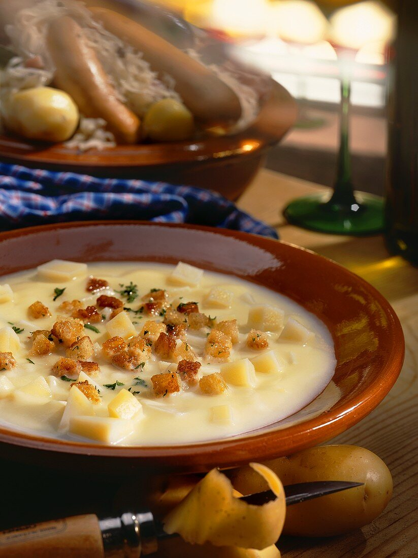 Potato soup with croutons and herbs; meat platter