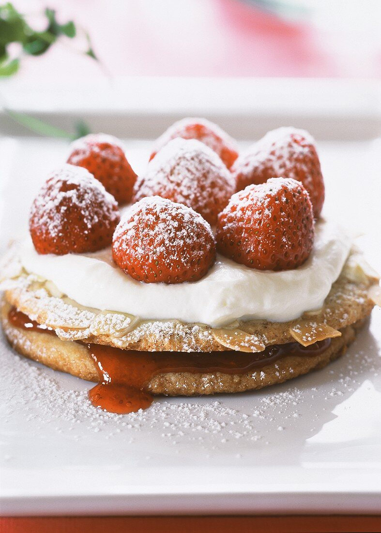 Strawberry and almond tartlet with cream and icing sugar