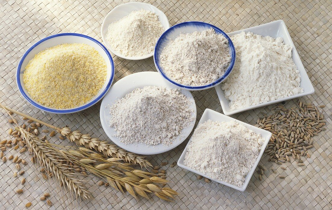 Various types of flour in bowls; cereal ears