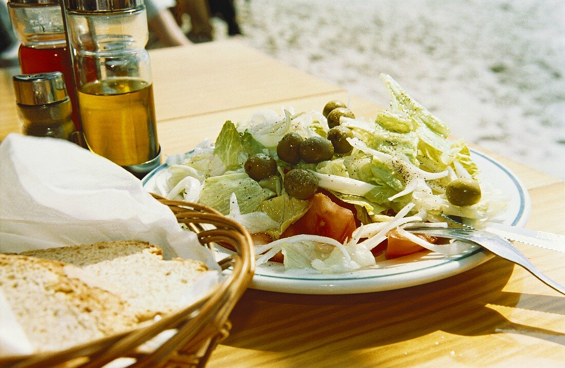 Greek salad with farmhouse bread on table in open air