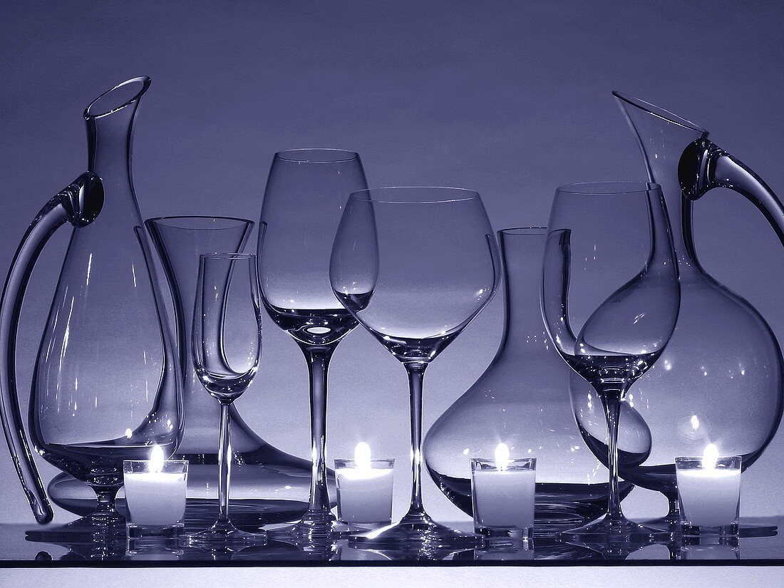 Still life with empty wine glasses, carafes and candles