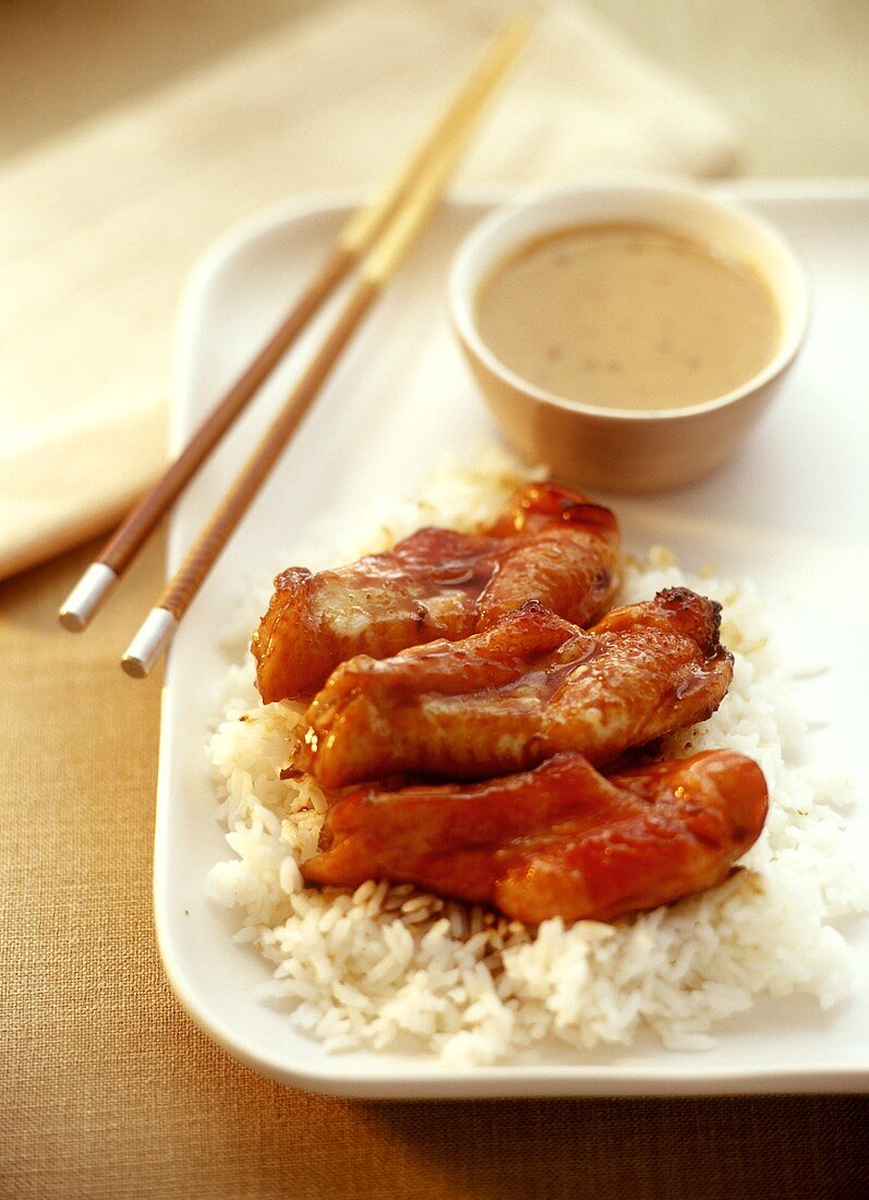 Chicken wings on rice with peanut sauce