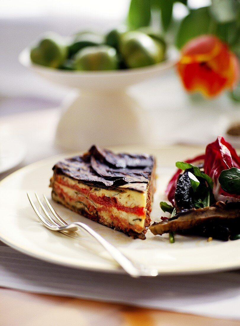 Piece of aubergine and pepper cake with salad