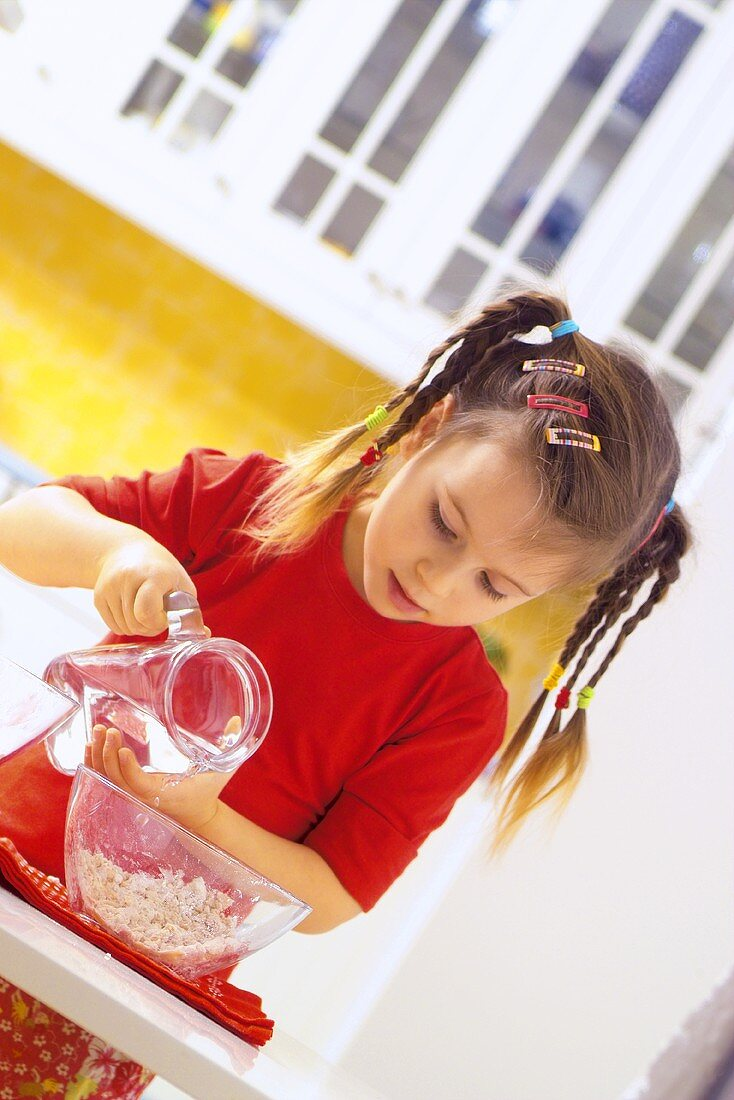 Small girl pouring water on to pizza dough
