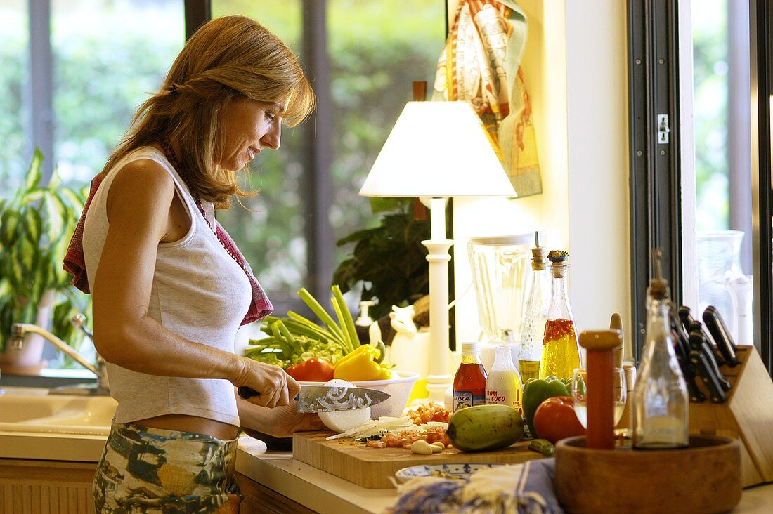 Woman in kitchen cutting up ingredients